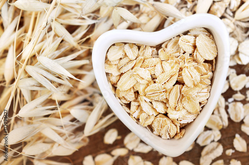 Oat groat in heart-shaped bowl, grain on oatmeal ears plants