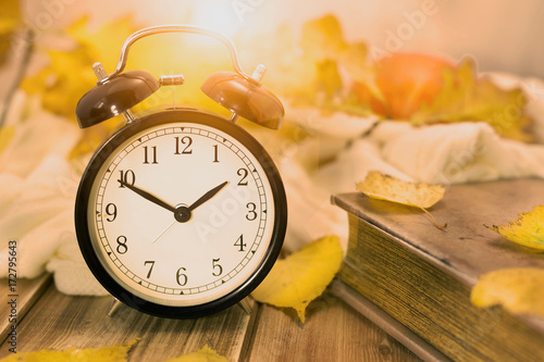 Old vintage alarm clock and old book with autumn yellow leaves on a wooden table.