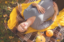 Pregnant Woman 30-35 Years Old Relaxing And Lying On A Picnic. Autumn Harvest. Pumpkins, Yellow Knitted Plaid