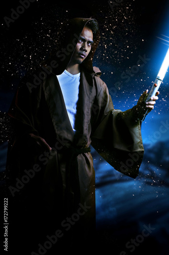 Photo  young warrior with brown hooded cape holding a light saber
