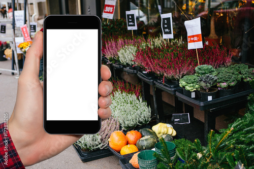 Hand with a phone in the background of a farm market. White screen, you can put your text here