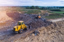 Aerial View On Bulldozers Working On The Landfill.