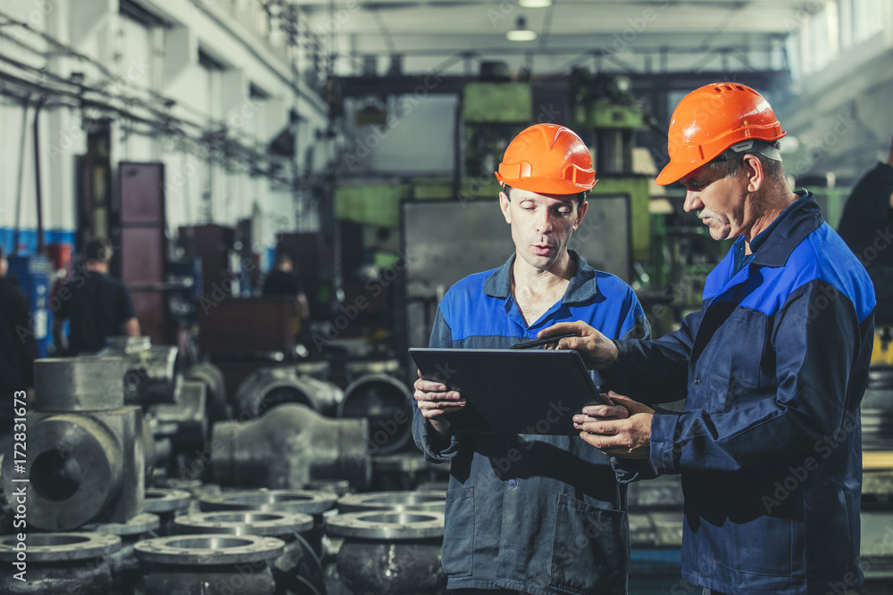 Fototapeta Two workers at an industrial plant with a tablet in hand, working together manufacturing activities
