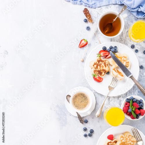 sniadanie-nalesniki-z-owocami-herbata-borowki-i-maliny-na-jasnym-tle