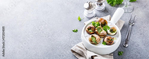 Bourgogne Escargot Snails with garlic herbs butter in white pan on light gray background. Healthy food concept with copy space. Banner.