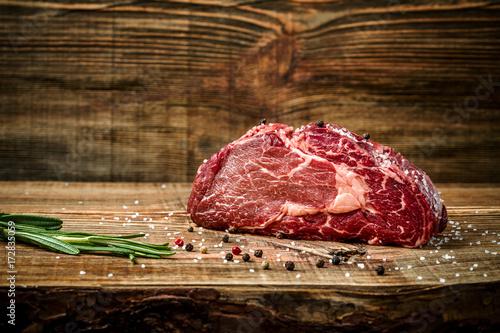 Dry aged Ribeye Steak with seasoning on wooden background. Fototapet