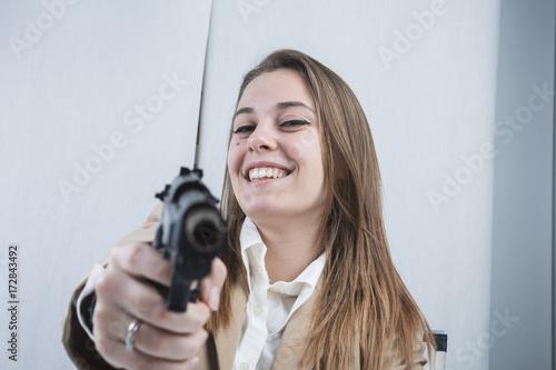 Photo Bella e sorridente segretaria bionda punta una  pistola scherzando