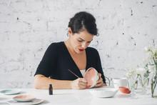 Woman Artisan Decorating Porcelain Bowl