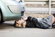 Woman, repairing broken car lying under it