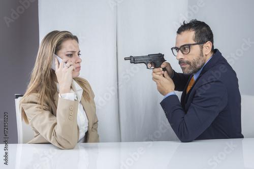 Capo ufficio punta una pistola alla segretaria che parla al telefono Canvas Print