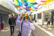 Doncaster Pride 19 Aug 2017 LGBT Festival, Man Wearing Rainbow Flag Hat Under Colourful Umbrella Canopy