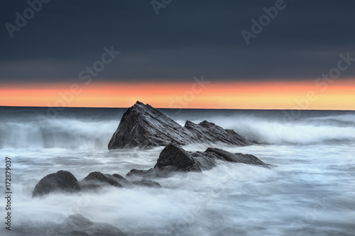 Photo  Bude, Cornwall, rocks at sunset with waves shots on slow shutter