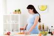 Leinwandbild Motiv pregnant woman cooking vegetable salad at home