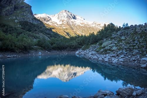 Keuken foto achterwand Turkoois Красивое горное озеро, отражение высоких скал в чистой воде, дикая природа Северного Кавказа, Домбай