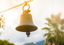 Bell Hanging On A Chain With Palms On Background