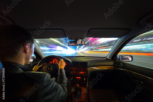 Fotomural  Driver in a car moves at fast speed at the autum night