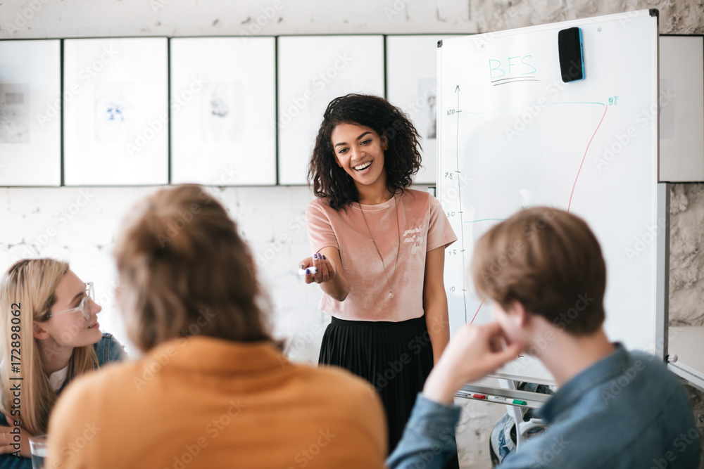 Fototapety, obrazy: Beautiful African American lady with dark curly hair standing near board and happily discussing new project with her colleagues in office. Young smiling business woman giving presentation to coworkers
