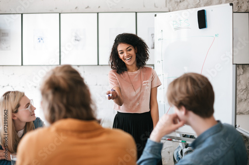 Fényképezés  Beautiful African American lady with dark curly hair standing near board and happily discussing new project with her colleagues in office