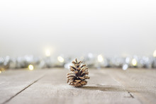 Pine Cone Sitting On Rustic Wooden Surface With Holiday Lights And Tinsel In Soft Focus