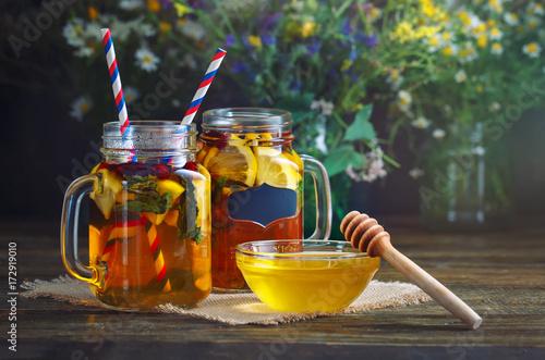 swiezy-miod-i-mrozona-herbata-z-cytryna-i-mieta-w-sloikach-z-uchem-oraz-slomkami