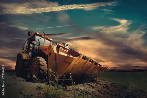 Vászonkép  Yellow tractor on sky background