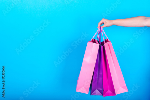 Fotografía  Female hand holding colorful shopping bags isolated on blue (cyan) background, free space, close up