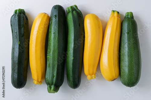 Yellow and green zucchinis in a row on white table, top view.