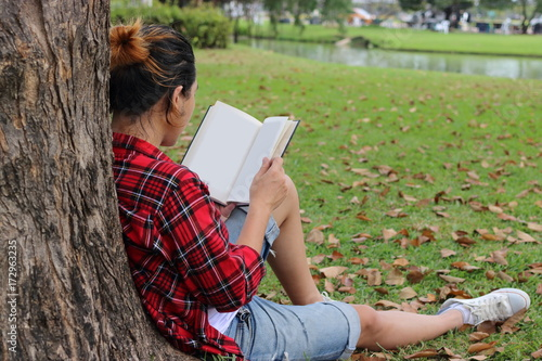Deurstickers Back view of young relaxed man in red shirt leaning against a tree and reading textbook in beautiful outdoor park.