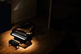 black grand piano at spot light in dark room