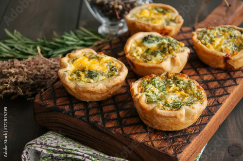 Savory mini quiches (tarts) on a wooden board. Flaky dough pies. Fresh rosemary and dry thyme on a wooden background.
