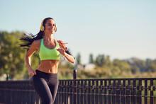 A Sports Girl In Headphones Runs Through The Park. Healthy Lifestyle.