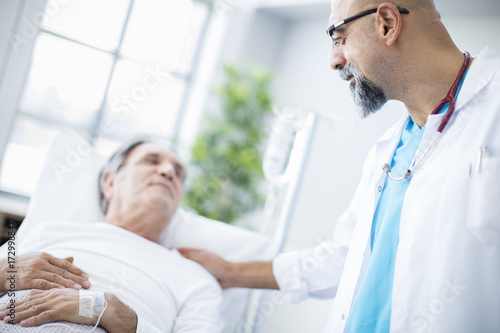 Fotografía  Doctor talking to patient in hospital bed