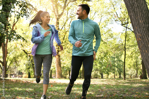 Young couple running together in park. Young people exercising. Fototapete