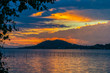 Sunset view from Songkhla lake, Southern Thailand, with cloudy sky and trees.