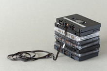 Stack Of Audio Cassette Tape With Loose Tape Spilling From Top Cassette.