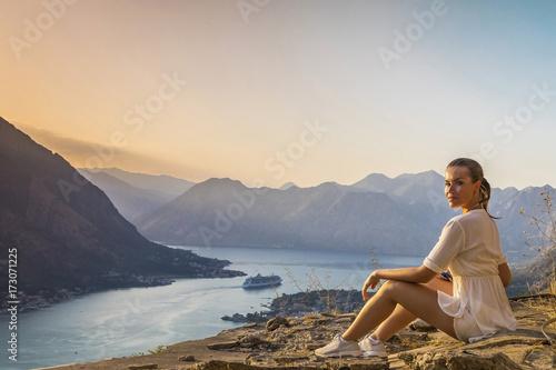 Fotomural девушка сидит на обрыве скалы с видом на залив и горы в Черногории