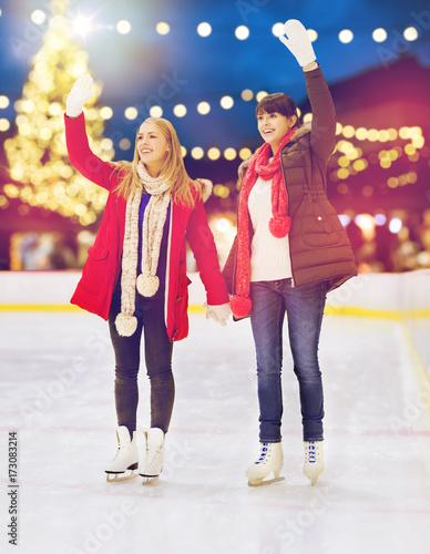 women waving hands at christmas skating rink