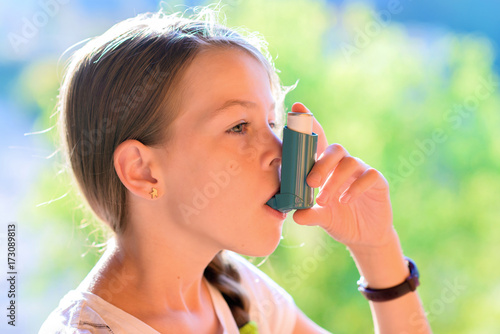 Photo Girl using asthma inhaler in a park