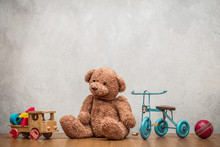 Retro Plush Teddy Bear, Old Toy Trike Bicycle, Obsolete Wooden Truck With Construction Blocks And Leather Ball Front Concrete Textured Wall Background. Vintage Style Filtered Photo