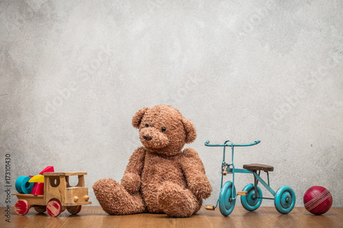 Obraz Retro plush Teddy Bear, old toy trike bicycle, obsolete wooden truck with construction blocks and leather ball front concrete textured wall background. Vintage style filtered photo - fototapety do salonu