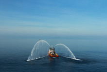 Fire Hose Boat Is Spraying Water On The Sea For Supporting Emergency Case Of Fire Of Offshore Oil And Gas Industry. Fire Fighting Boat Sprays Water On The Sea.