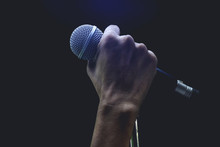 Man Hands Holding Microphone On Stand.