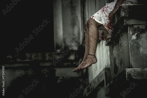 Photo Zombie woman sitting on the edge of the window in an abandoned building on Halloween