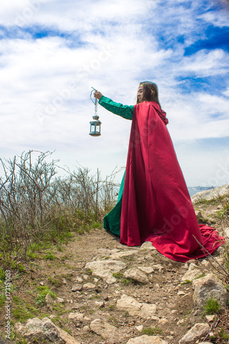 Photo  girl by ocean with lantern and red cape
