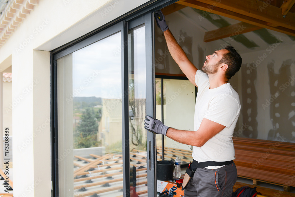 Fototapeta handsome young man installing bay window in a new house construction site