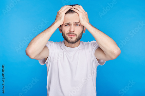Fotografia  Portrait of forgetful young European or American customer or employee wearing white t-shirt looking with shocked and guilty expression, holding hands on his head, opening mouth widely