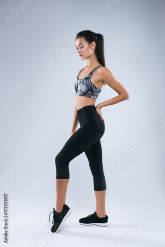 Beautiful and sexy sport woman posing as sportwoman in studio over gray background Fototapete