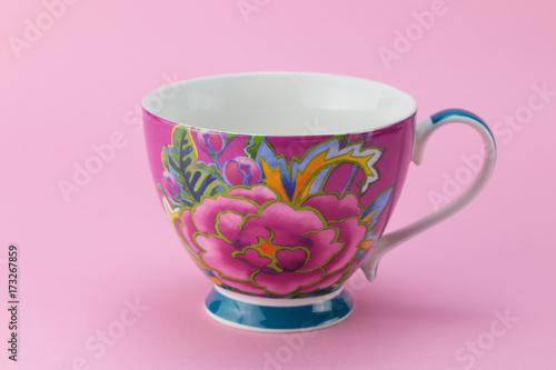 Side view of empty tea or coffee cup with pink and purple flower decoration isolated on pink background