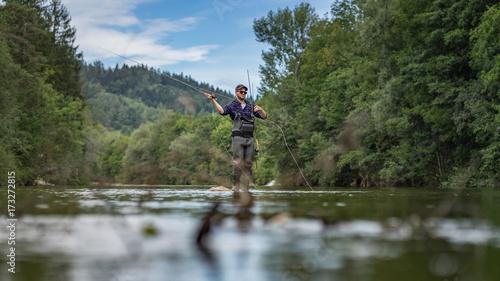 Fotografia, Obraz Angler mit Wathose und Fliegenrute im Wasser beim Angeln bei Sonne im klaren Flu