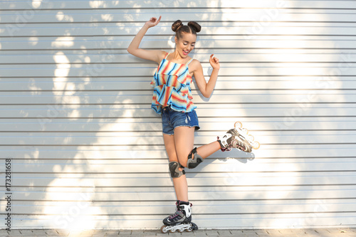 Young woman on roller skates near fence